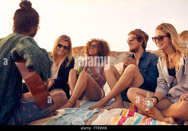 Group of young people listening to friend playing guitar outdoors. Diverse group of friends hanging out at beach. - Stock-Bilder