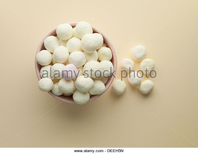 Bowl of white bon bons and one pink mint - Stock Image