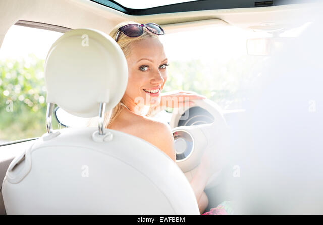 Rear view portrait of happy woman driving car - Stock Image