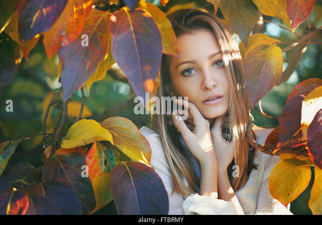Beautiful young woman posing among colorful autumn leaves - Stock Image