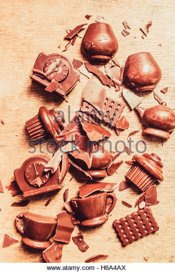 Artistic food still life on smashed flakes and chocolate chunks in shapes and forms of delicious kitchen icons - Stock Image