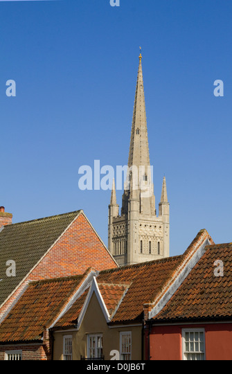 The spire of Norwich Cathedral soars above rooftops of houses. - Stock Image