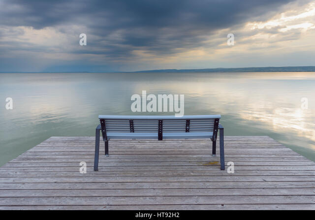 Bench on Wooden Jetty at Sunset at Weiden, Lake Neusiedl, Burgenland, Austria - Stock Image