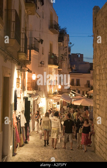 Spain Baleares island Ibiza town at twilight fashion shops and souvenirs in Dalt vila people - Stock Image