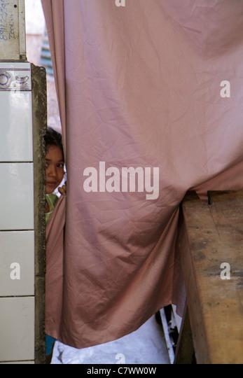 Nicaragua Managua Bolonia Hispanic girl shy behind curtain looking peek peeking - Stock Image