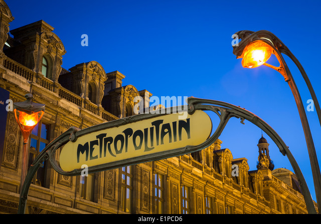 Metro sign and lights at Palais Royal/Musee du Louvre Metro stop with Musee du Louvre beyond, Paris France - Stock Image