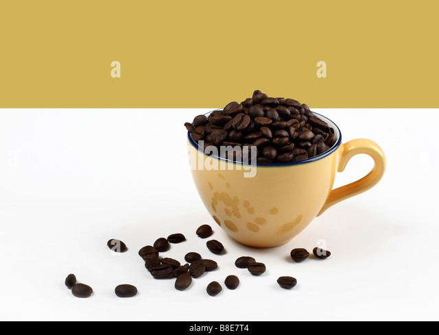 Coffee cup filled with organic coffee beans - Stock Image