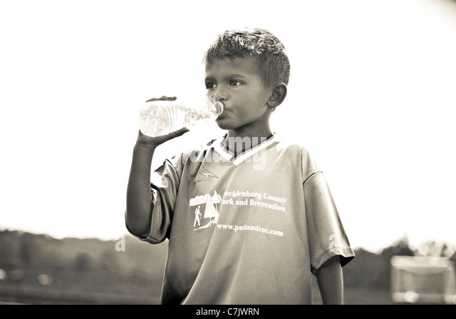 portrait of boy drinking bottled water - Stock Image