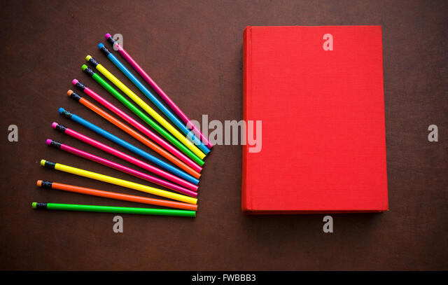 Wooden writer desktop with colorful pencil and red empty cover book - Stock Image