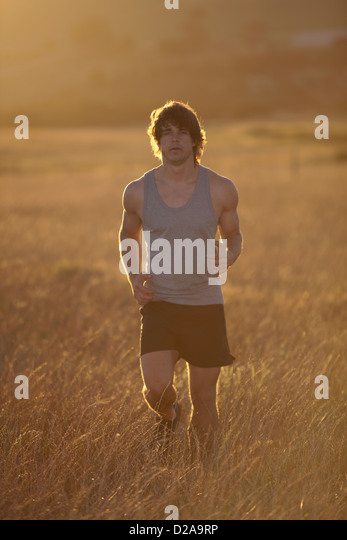 Man running in tall grass at sunset - Stock Image