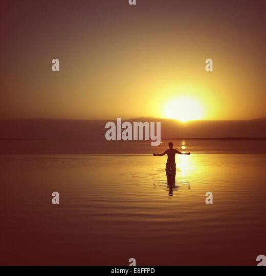 Silhouette of a Man standing in the Dead Sea at sunset, Israel - Stock Image