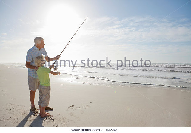 Grandfather and grandson with fishing rod on sunny beach - Stock Image