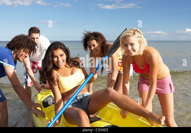 Teenagers in sea with canoe - Stock Image