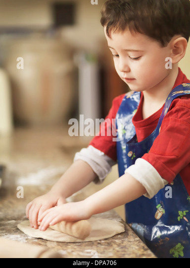 Child kneading dough with rolling pin - Stock-Bilder