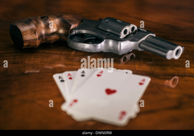 Risky gambling concept. Gun and four aces cards on wooden table. - Stock Image