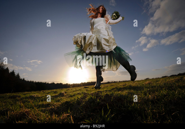 A bride jumping for joy in a Becky Drinan designed dress wearing wellington boots. Picture by Jim Holden. - Stock Image