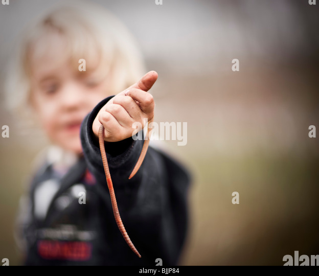 Young boy holding up a worm. - Stock Image