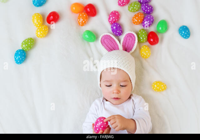 Baby boy in bunny hat lying on green blanket with easter eggs - Stock Image
