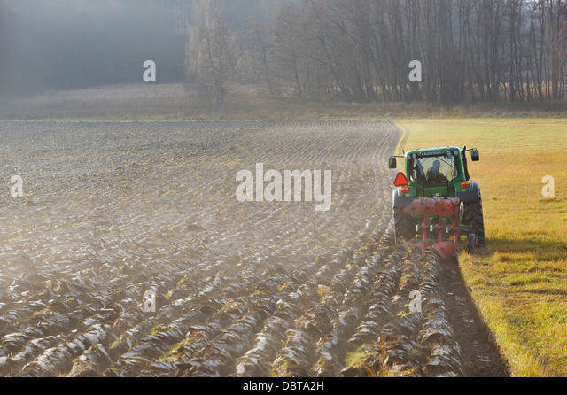 Tractor plowing field - Stock Image