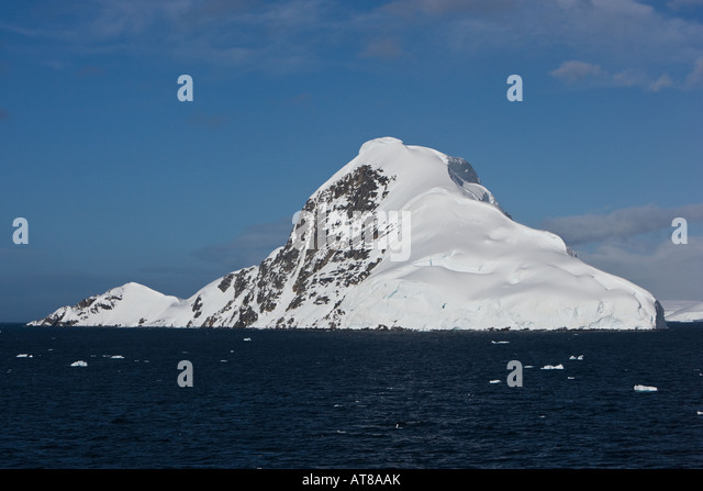 Snow capped island surrounded by sea against a blue sky background - Stock Image