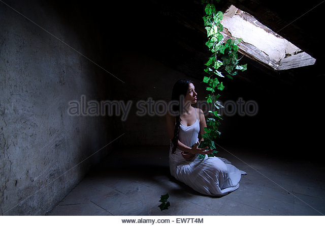 Woman sitting in an empty abandoned attic - Stock Image