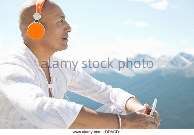 Mature man listening to music outdoors - Stock Image