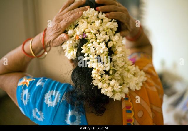 An elderly woman arranges flowers in her hair in her bedroom, Janakpuri, New Delhi, India - Stock-Bilder