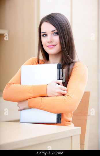 Beautiful casual woman hugging her laptop at home - Stock Image