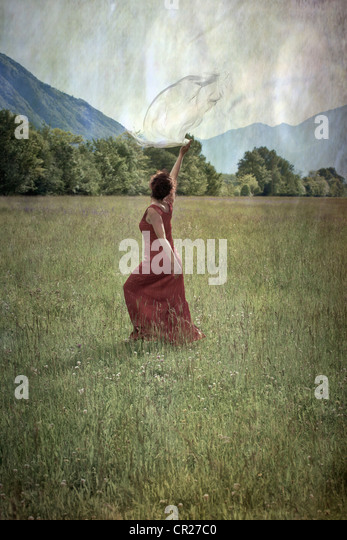 a woman in a red dress dancing on a lawn - Stock Image