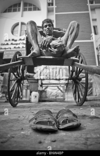 A rickshaw puller takes a well earned break on the streets of Kolkata (formally known as Calcutta) - Stock Image