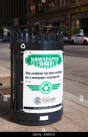 Bin modified for newspaper recycling on downtown street - Stock Image