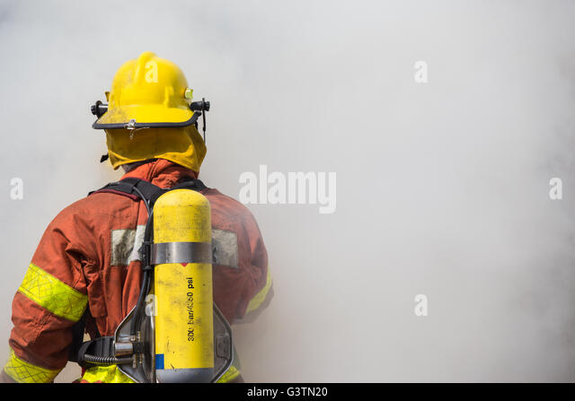 single fireman is working  and surround with smoke - Stock Image