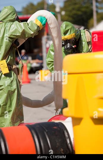 HazMat firefighters arranging chemical HazMat boom to contain contamination - Stock Image