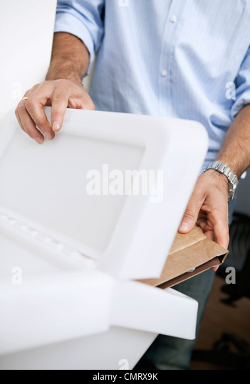 Man tossing cardboard in a box - Stock Image