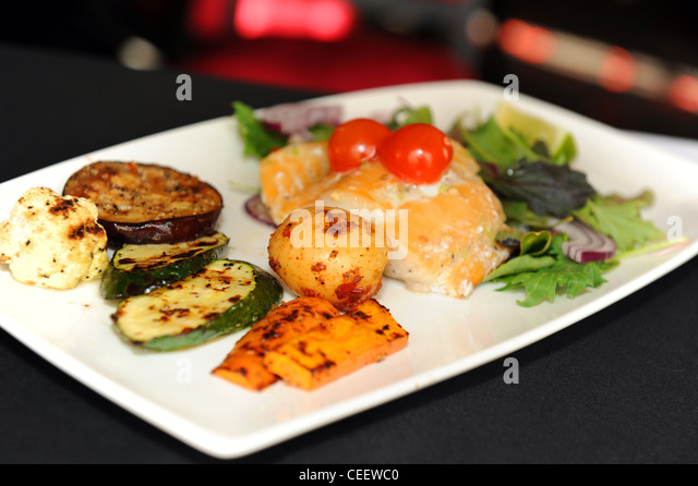 Grilled fish, vegetables and salad - Stock Image