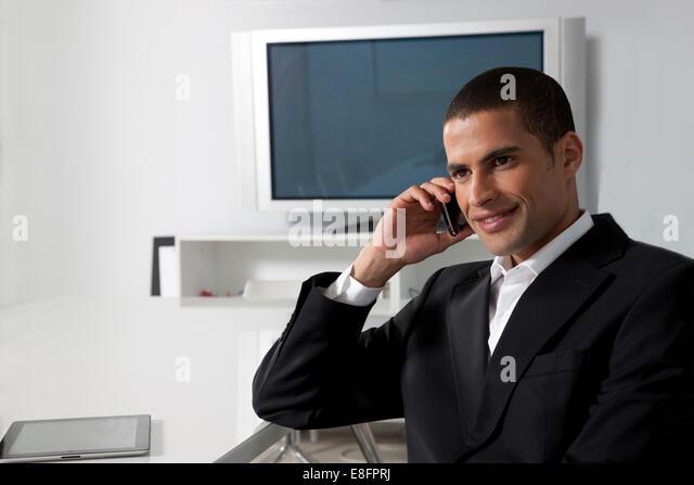 Businessman on cellphone in contemporary office - Stock-Bilder
