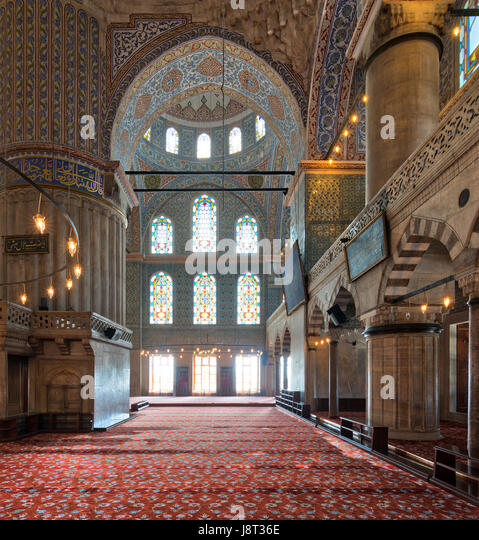 Interior of Sultan Ahmed Mosque (Blue Mosque), with a huge pillars, arches, and colored stained glass windows, Istanbul, - Stock Image