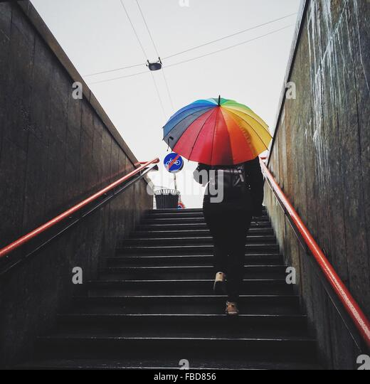 Rear View Of Woman Holding Umbrella And Walking On Staircase - Stock Image