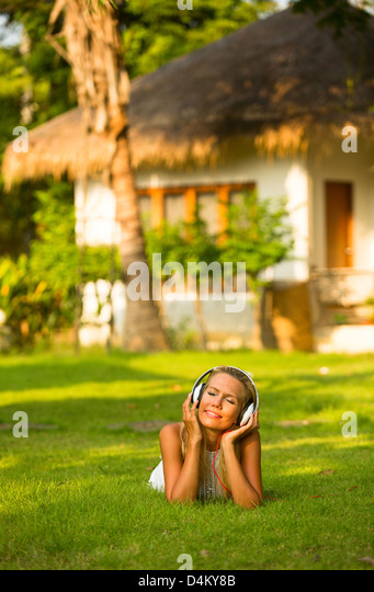 Beautiful emotional girl with headphones enjoying nature and music at sunny day. - Stock Image