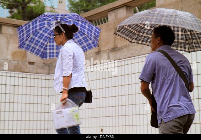 China Beijing Wangfujing Subway Station Line 1 public transportation Asian woman man umbrella weather entrance exit - Stock Image