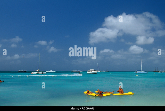 Aruba Palm Beach tourists with yellow float - Stock Image