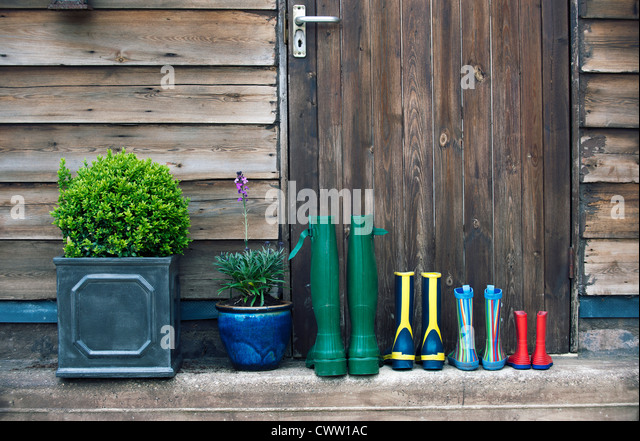 Rain boots and plants on porch - Stock Image