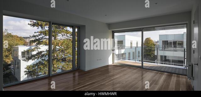 Interior third floor apartment showing glass sliding doors to exterior. Dunluce Apartments, Ballsbridge, Ireland. - Stock-Bilder