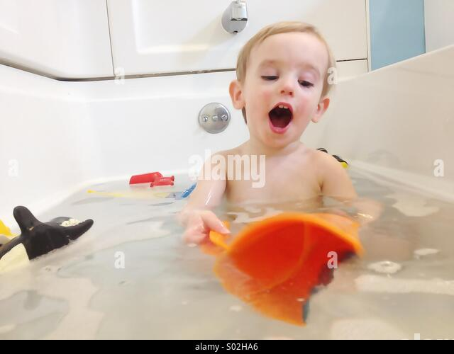 Toddler boy playing in bath - Stock Image