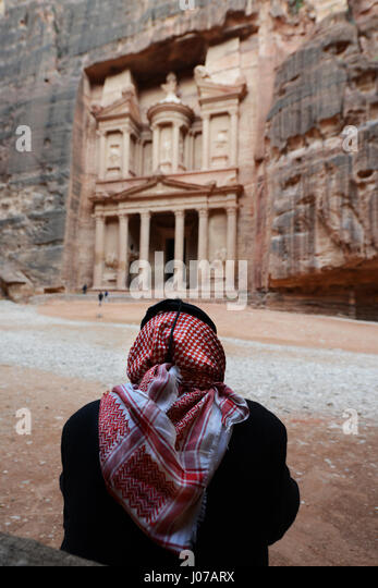 A Bedouin man sitting by the Treasury rock carved tomb in the ancient city of Petra, Jordan. - Stock Image