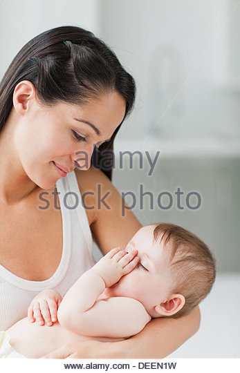 Close up of mother holding sleeping baby sucking thumb - Stock Image