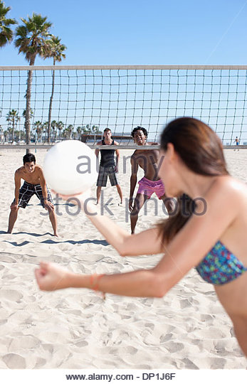 Woman playing beach volleyball with friends - Stock Image