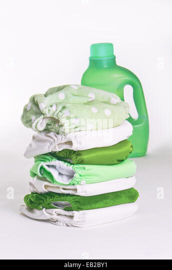 Environmentally friendly cloth diapers with a green container of laundry detergent - Stock Image