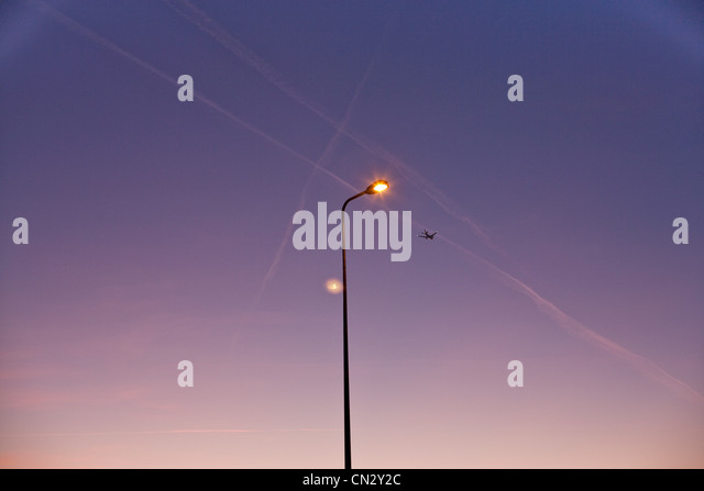 Airplane and street light at dusk - Stock Image