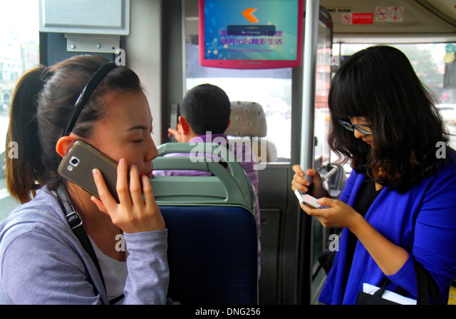 Beijing China Guang An Men Nei Da Jie Guanganmen Outer Street public bus onboard passengers riders Asian woman smartphone - Stock Image